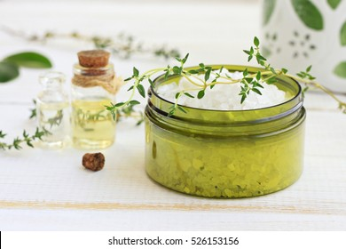 Green jar of sea salt, essential oil, fresh thyme sprig. Herb infused bath blend. Botanical skincare cosmetic and aromatherapy. Facial scrub