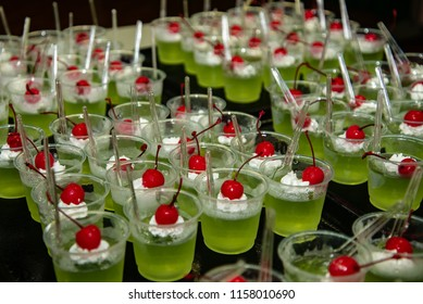 green jelly dessert with whipped cream and cherry