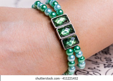 Green jewerly bracelet on hand in close-up