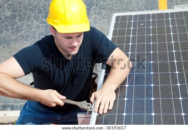 Green job series - young electrician repairs solar panel.