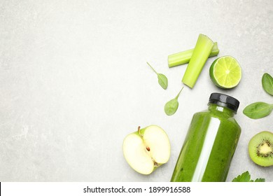 Green juice in bottle and fresh ingredients on light grey table, flat lay. Space for text