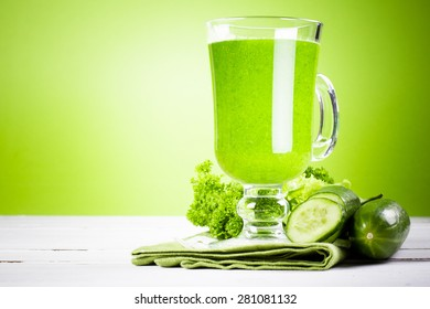 Green juice on white wooden table against green background
