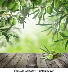 Green kalamata olives, abstract bokeh light and empty wooden table with copy space on green background. Traditional greek olive oil food background