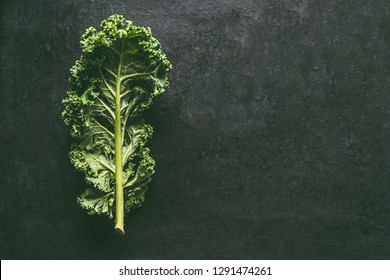 Green kale leaf on dark background, top view with copy space. Healthy detox vegetables . Clean eating and dieting concept. Top view with copy space. Health kale benefits