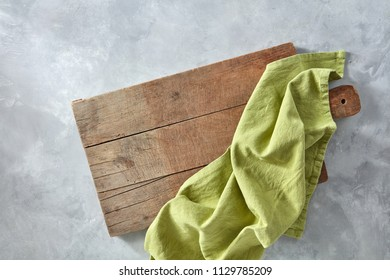 Green kitchen napkin on an old wooden board on a gray concrete background with copy space. Top view