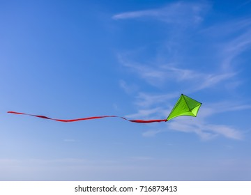 Green kite flying against a cloudy blue sky.