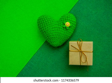 green knitted heart and gift box on a green background, a symbol of love to congratulate the holiday