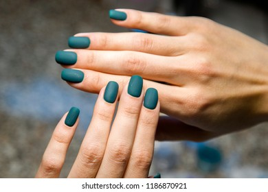 green lacquer applied to nails in the salon of manicure