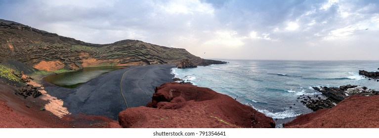 green lagoon and wild beach on the Atlantic Ocean in El Golfo village, Lanzarote. A rocky beach with fishing boats surrounded by volcanic mountains