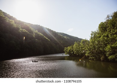 The Green Lake of Hamori in Lillafure near Miskolc, Hungary. Spring landscape with sunrays covering the mountains. The solar path on the water. Unrecognizable people on boat