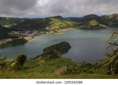 Green lake - Lagoa Verde at Sete Cidades. Fresh green spring nature. Hills and mountains around the lake. Cloudy sky. Sao Miguel, Azores Islands, Portugal.