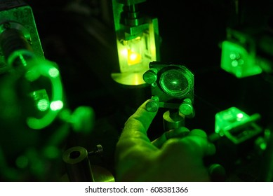 A green laser illuminates test tube with a yellow substance in the laboratory.