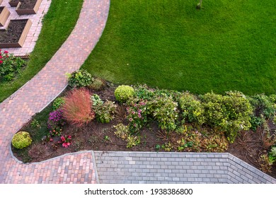 Green lawn, bright bushes and beautiful paving stones. Top view, view from the window. Path in the garden.