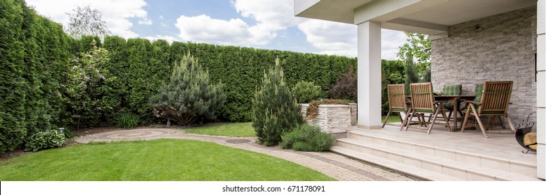 Green lawn and terrace with garden furniture