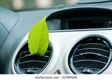 Green leaf in the car air outlet. Clean air conditioning concept.