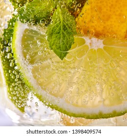 Green leaf of mint, pieces of lemon and lime with bubbles in a transparent glass. Macro photo of summer cold mojito