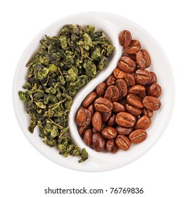 Green leaf tea versus coffee beans in Yin Yang shaped plate, isolated on white