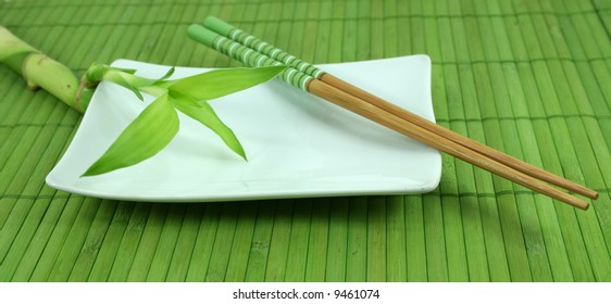A green leafy bamboo shoot sits on a white plate with chopsticks on a green bamboo mat.