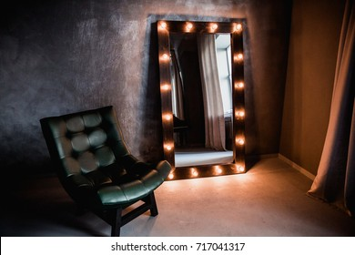 green leather armchair and long dressing mirror with lighted lamps in a frame on the floor in a dark room against the background of a gray aged wall
