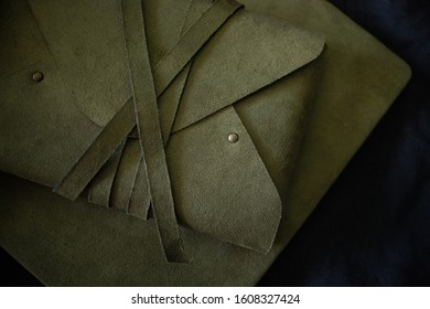 Green leather envelope on dark background