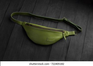 green leather fanny pack on black background