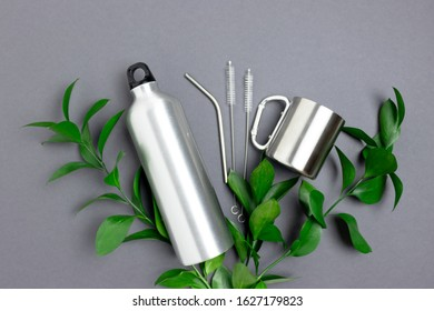 Green leaves, bottle, mug, metal tube and cleaning brush. Zero waste accessories for drinking on dark gray background.