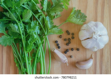 Green leaves coriander or cilantro, garlic and black pepper put on wooden table in top view flat lay with copy space. Food preparation concept for fresh vegetable and spices.