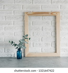 green leaves eucalyptus in a blue vase and wooden photoframe against a white brick wall Scandinavian style minimalism
