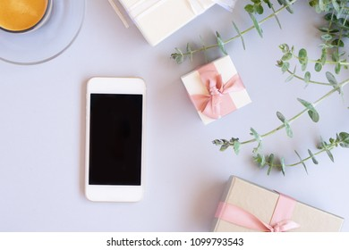 Green leaves with gift boxes and modern phone on blue table with copy space, flat lay scene