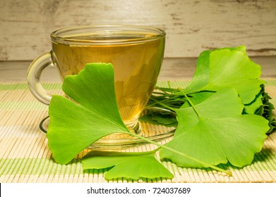 Green leaves from a gingo biloba tree on a wooden table with a cup of tea