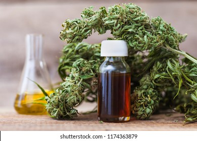 Green leaves of medicinal cannabis with extract oil on a wooden table