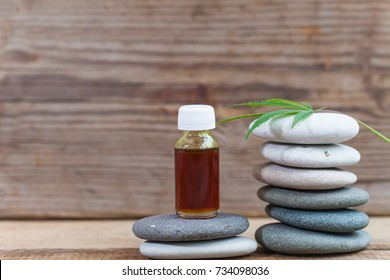 Green leaves of medicinal cannabis with extract oil on a wooden table pebble pyramid