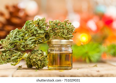 Green leaves of medicinal cannabis with extract oil on a wooden table on a Christmas New Year's background
