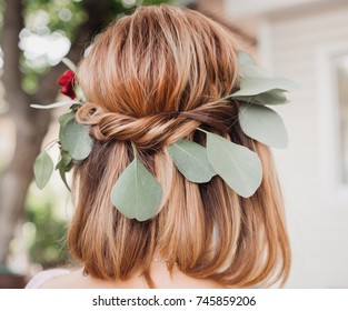 Green leaves and red flowers in bride's hair