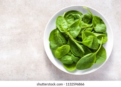 Green leaves of spinach on plate, healthy diet, vegan food concept