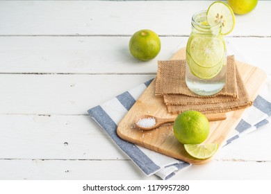 Green lemon in soda bottle on cutting bord and white table