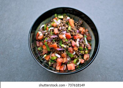 Green lentils, tomato and onion salad bowl, top view.