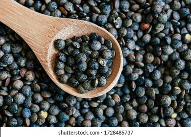 Green lentils in a wooden spoon and lentils background