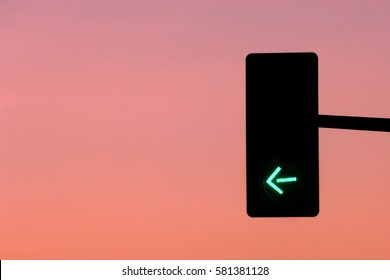Green light arrow on traffic road sign with sunset background