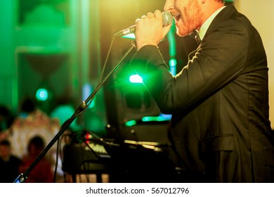 Green light illuminates bearded man in black suit singing on the stage