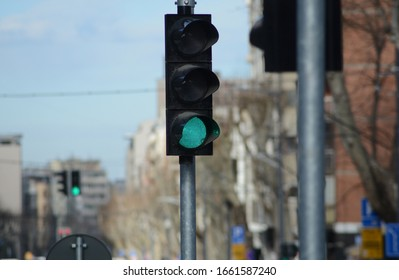 a green light on a public traffic light on a metal pole in the city