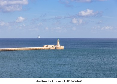 green lighthouse in Valette Malta in the mediterranean sea on a sunny day and a cruiseship approaching