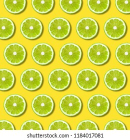 Green lime slices pattern on vibrant yellow color background. Minimal flat lay food texture