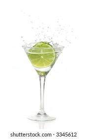Green lime splashing into a martini glass
