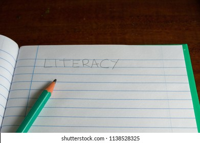 green lined notebook with white sheets written the word literacy in plain letters