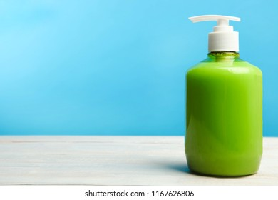 Green liquid hand soap on wooden table on blue background.
