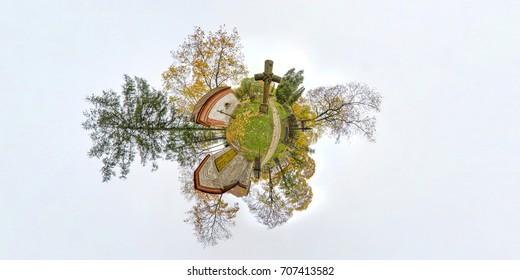 Green little planet with old catholic churchyard, green trees and grass, without clouds. 360 viewing angel. Tiny planet with big cross.