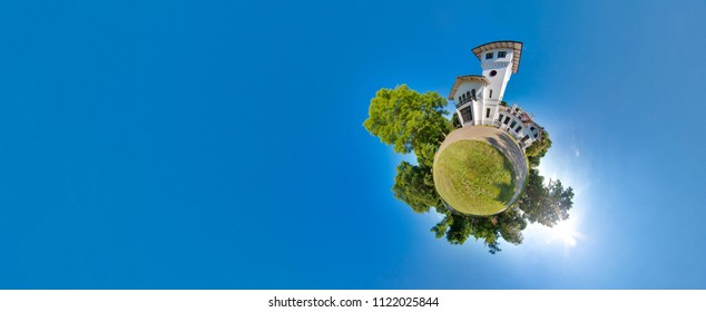 Green little planet with trees, soft blue sky and building. Tiny planet sunset near the castle. 360 viewing angle. Planet Earth.