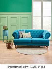 Green living room, classic wall background and window with blue sofa, coffee table, vase of plant.