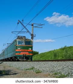 green locomotive going on railway against blue sky